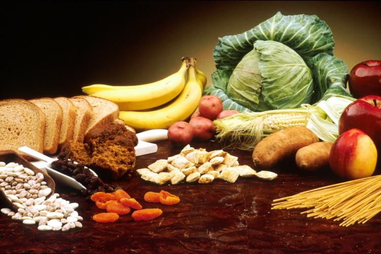 Uma mesa contendo: feijão, um pão fatiado de pão escuro, bananas, muffins, batatas pequenas, repolho, uma espiga de milho, cereal, inhame, maçãs, uma nectarina e um pouco de esparguete.